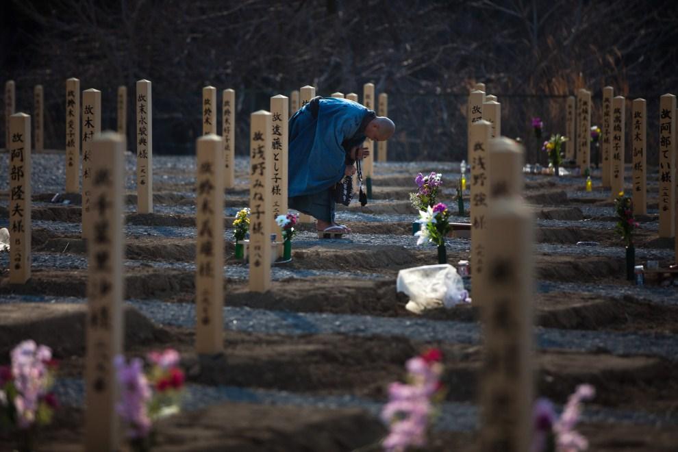34. JAPONIA, Onagawa, 11 marca 2011: Buddyjski mnich modli się na cmentarzu, gdzie pochowano ofiary tsunami. AFP PHOTO / YASUYOSHI CHIBA