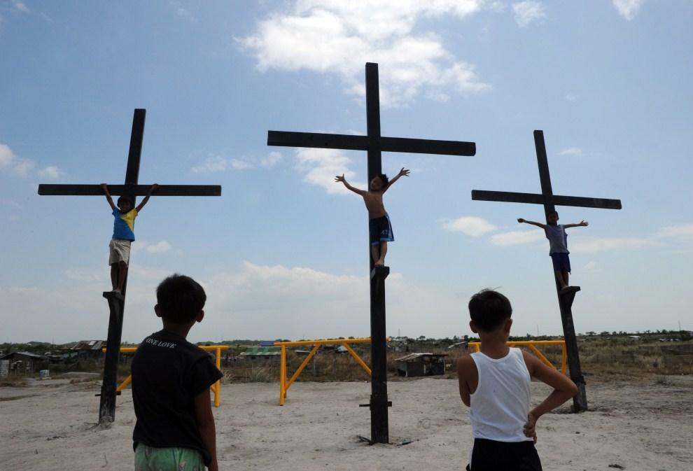 3. FILIPINY, Cutud, 21 kwietnia 2011: Dzieci bawią się na drewnianych krzyżach przygotowanych na obchody Wielkiego Piątku. AFP PHOTO / TED ALJIBE