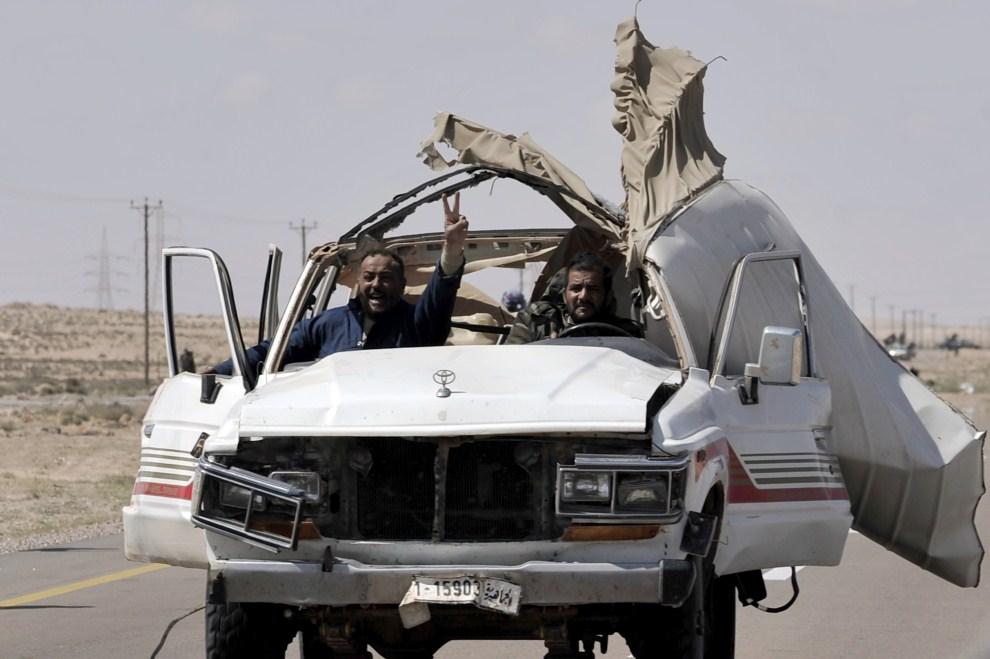 5. LIBIA, Brega, 31 marca 2011: Rebelianci wracają z linii frontu na przedmieściach Bregi. AFP PHOTO / ARIS MESSINIS