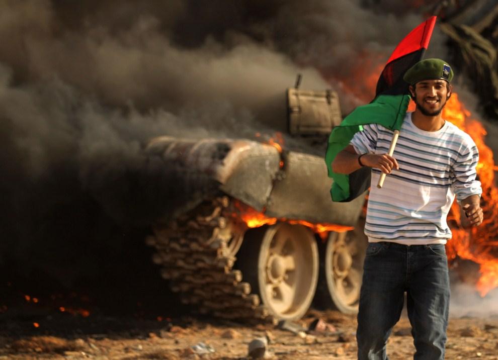 7. LIBIA, Adżdabija, 26 marca 2011: Rebeliant na tle płonącego czołgu lojalistów. AFP PHOTO/PATRICK BAZ