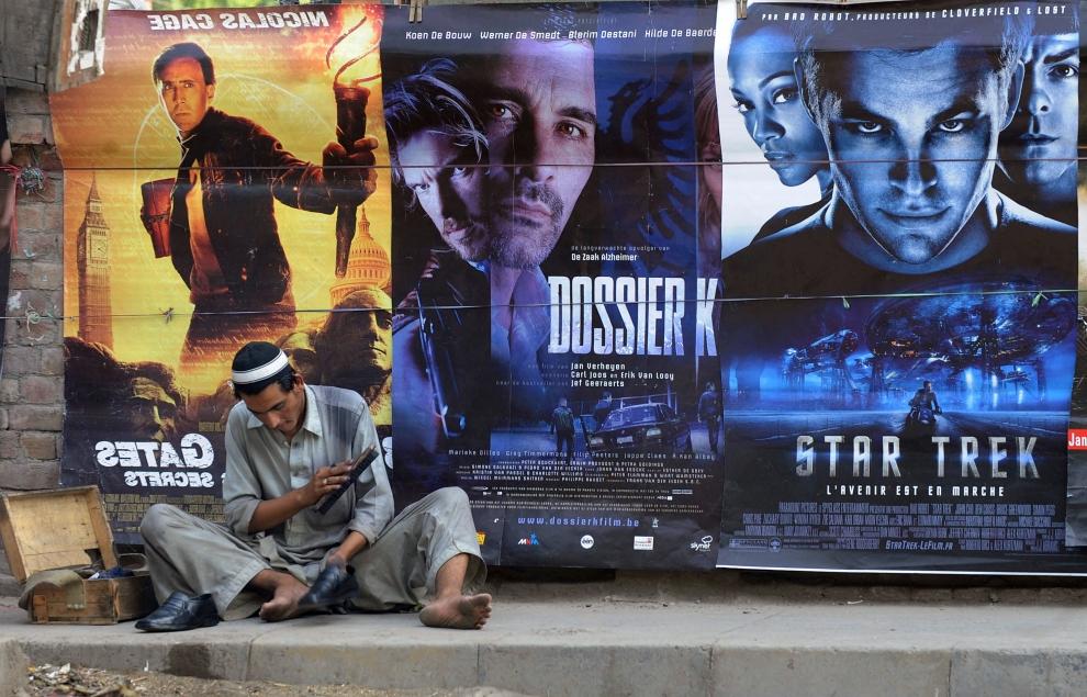 8. PAKISTAN, Lahore, 14 maja 2010: Pucybut pod ścianą oklejoną plakatami filmowymi. AFP PHOTO/ARIF ALI