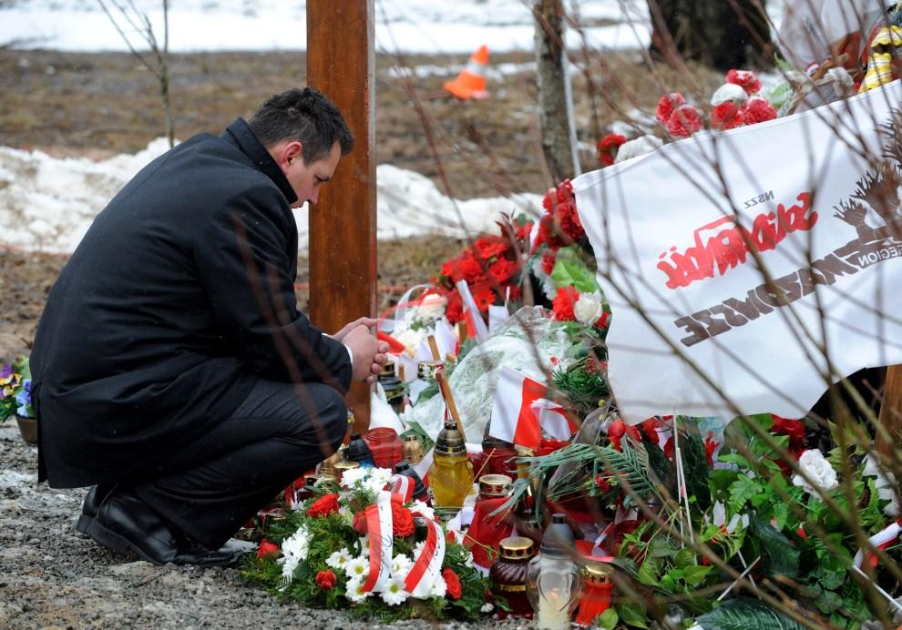 8. ROSJA, Smoleńsk, 10 kwietnia 2011: Mężczyzna zapala znicz w miejscu gdzie przed rokiem rozbił się Tu-154M. AFP PHOTO / NATALIA KOLESNIKOVA
