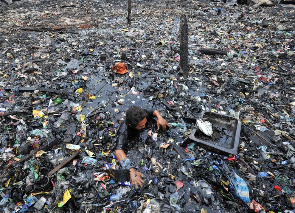 9. FILIPINY, Manila, 7 kwietnia 2011: Mieszkaniec slumsów przeszukuje ruiny spalonych zabudowań. AFP PHOTO/TED ALJIBE