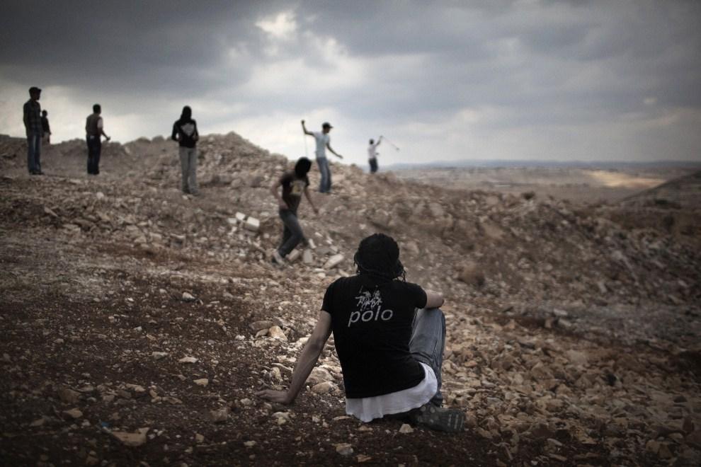 10. ZACHDONI BRZEG, Anata, 15 maja 2011: Palestyńczyk przygląda się pozostałym protestującym, rzucającym kamieniami w kierunku izraelskich żołnierzy. AFP PHOTO / MARCO   LONGARI