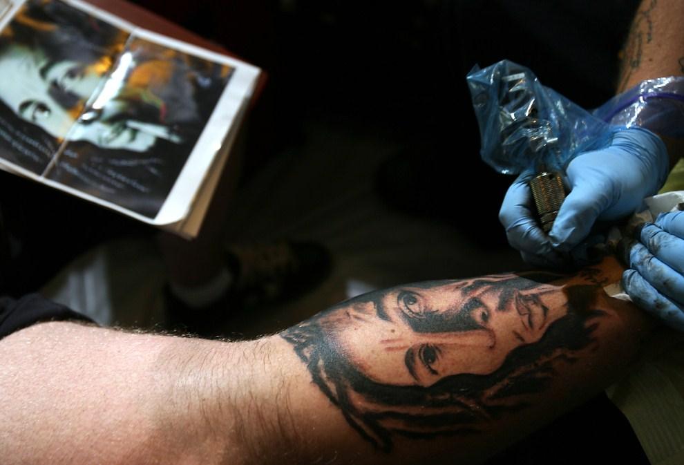 10. USA, Los Angeles, 15 września 2006: Jason Riedel tatuuje wizerunek Boba Marleya na nodze swojego klienta. AFP PHOTO/GABRIEL BOUYS