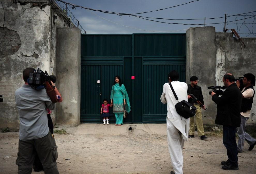 11. PAKISTAN, Abbottabad, 5 maja 2011: Kobieta pozuje do zdjęć przed bramą do posiadłości, gdzie ukrywał się Osama bin Laden. AFP PHOTO/Asif HASSAN