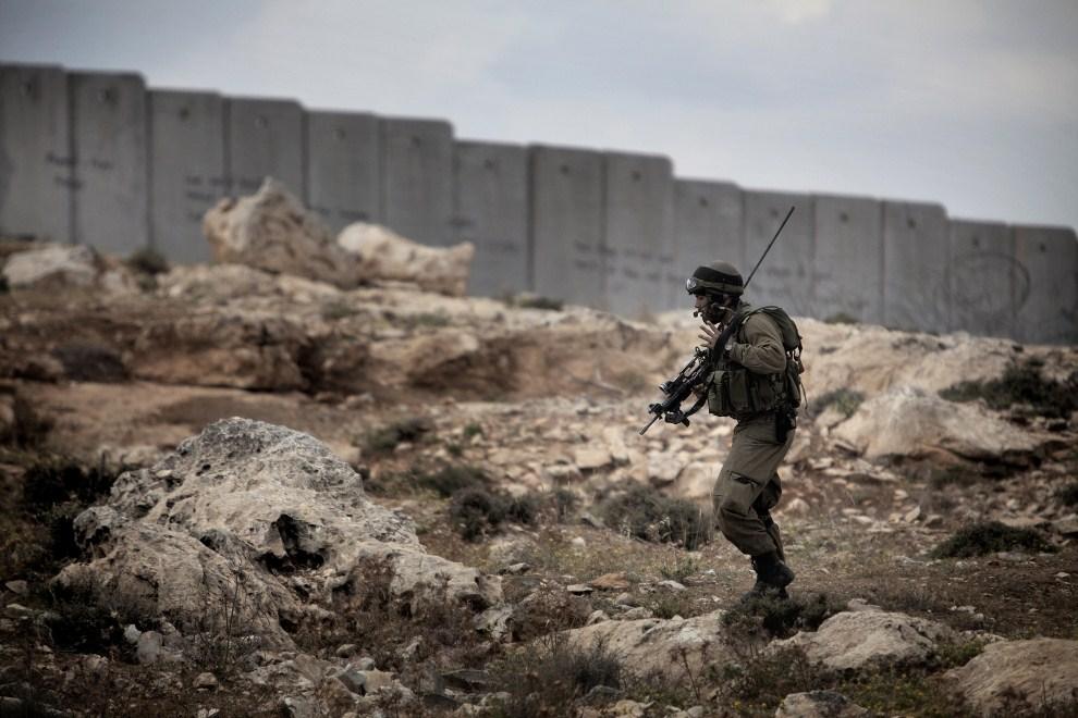 11. ZACHDONI BRZEG, Anata, 15 maja 2011: Izraelski żołnierz zajmuje pozycję wzdłuż muru granicznego podczas zamieszek. AFP PHOTO / MARCO LONGARI