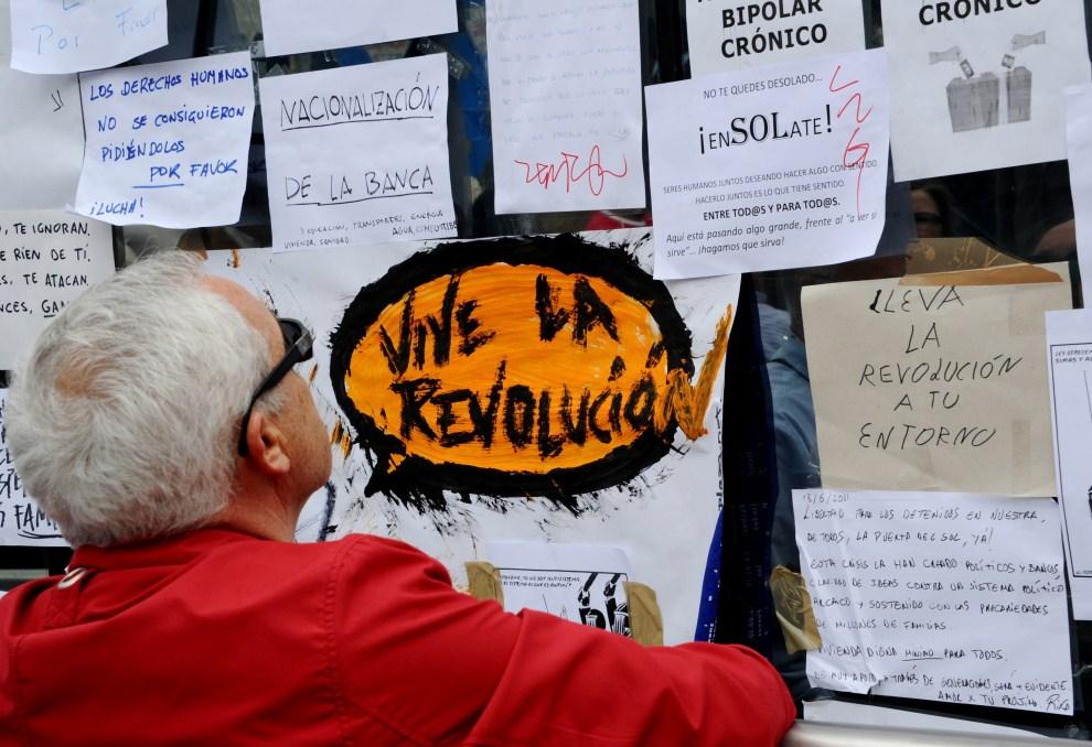 12. HISZPANIA, Madryt, 19 maja 2011: Mężczyzna czyta ulotki rozklejone na stacji metra prowadzącej do  Puerta del Sol. AFP PHOTO / DOMINIQUE FAGET