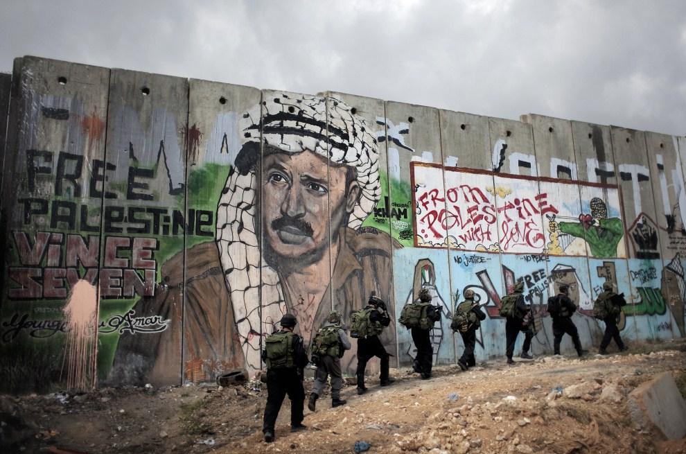 13. IZRAEL, Kalandia, 15 maja 2011: Izraelski oddział mija fragment muru granicznego z graffiti przedstawiającym Jasira Arafata. AFP PHOTO / MARCO LONGARI