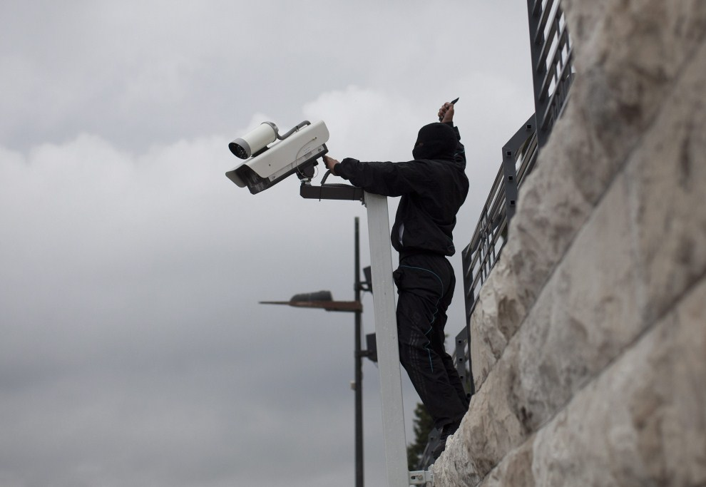 15. IZRAEL, Ras al-Amud, 14 maja 2011: Zamaskowany Palestyńczyk odcina kable kamery monitoringu. PAP/EPA.