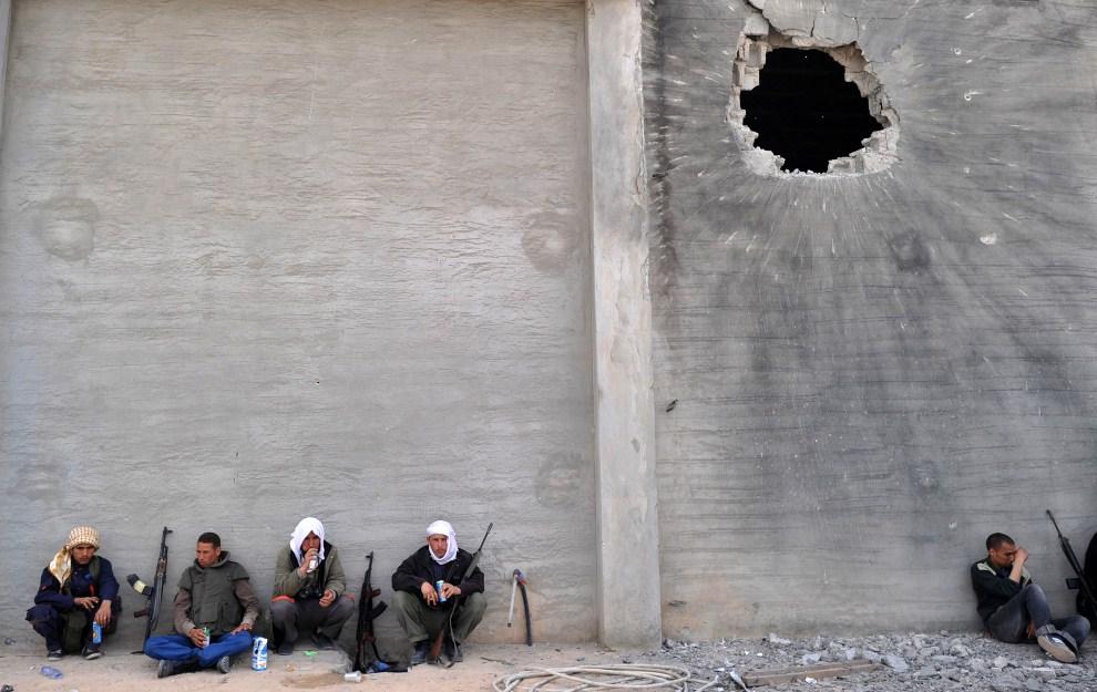 16. LIBIA, Misrata, 24 kwietnia 2011: Rebelianci odpoczywają pod ścianą ostrzelanego budynku. AFP PHOTO/CHRISTOPHE SIMON
