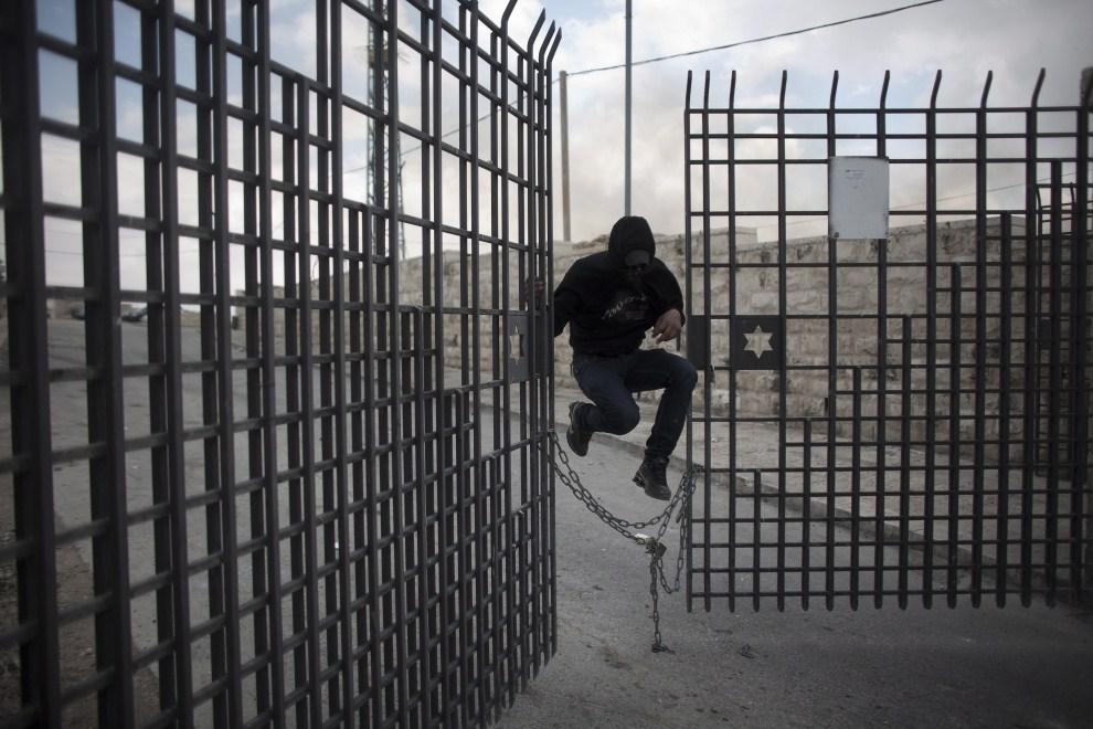 16. IZRAEL, Ras al-Amud, 14 maja 2011: Palestyńczyk przeskakuje przez zabezpieczenia bramy cmentarnej uciekając przed służbami pożądkowymi. PAP/EPA.