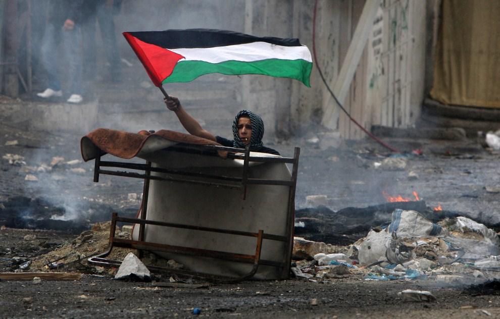 18. IZRAEL, Szuafat, 15 maja 2011: Palestyńczyk ukrywający się podczas zamieszek. AFP PHOTO /AHMAD GHARABLI