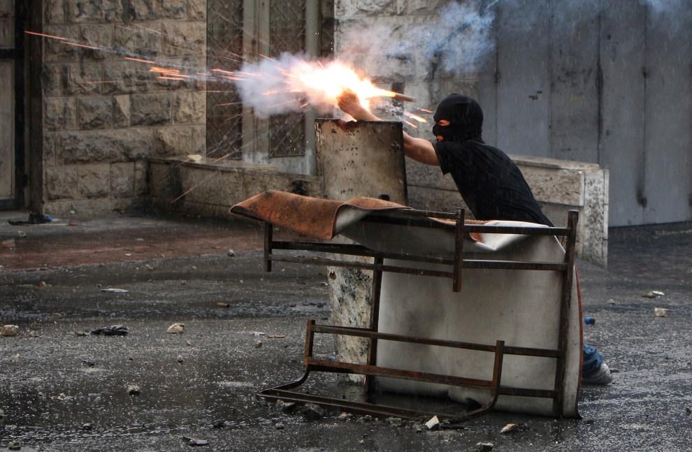 19. IZRAEL, Szuafat, 15 maja 2011: Palestyńczyk odpala petardę w kierunku oddziałów wojskowych. AFP PHOTO /AHMAD GHARABLI