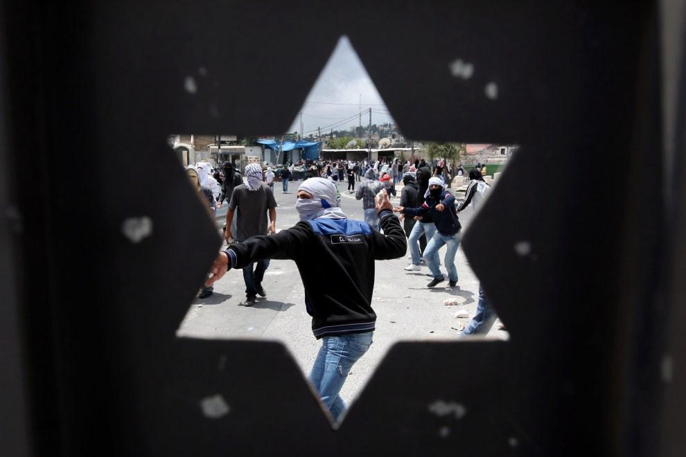 1. IZRAEL, Jerozolima, 14 maja 2011: Palestyńczycy rzucający kamieniami widziani przez bramę prowadzącą na Górę Oliwną. PAP/EPA.