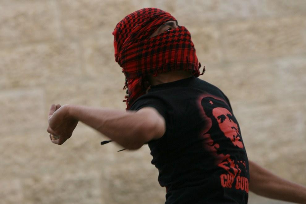 20. ZACHODNI BRZEG, Hebron, 15 maja 2011: Palestyńczyk rzuca kamieniem w kierunku izraelskich żołnierzy. AFP PHOTO / HAZEM BADER