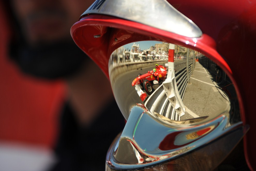 20. MONAKO, 29 maja 2011: Bolid prowadzony przez Felipe Massę odbija się w hełmie i goglach strażaka. AFP PHOTO / Tom Gandolfini