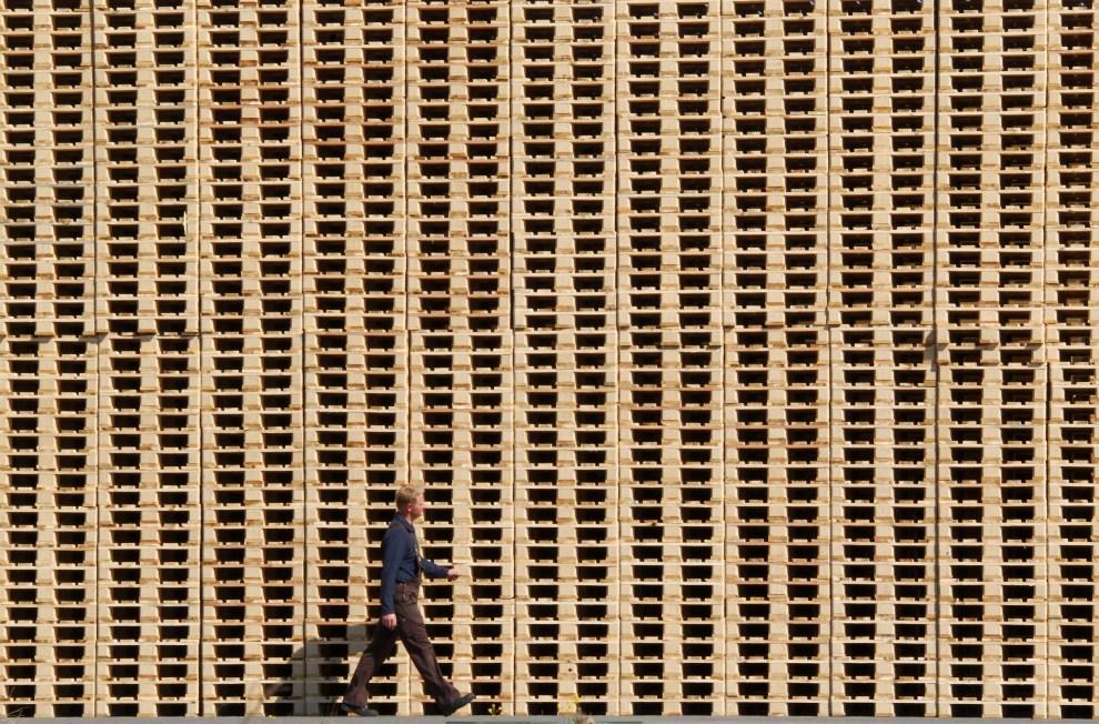 21. NIEMCY, Wismar, 5 maja 2011: Pracownik fabryki przechodzi obok sterty  palet. AFP PHOTO / JENS BUTTNER GERMANY OUT