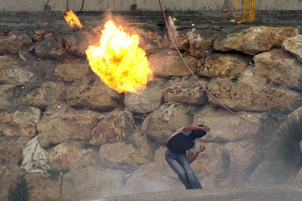 21. IZRAEL, Jerozolima, 13 maja 2011: Palestyńczyk rzuca granatem zapalającym domowej produkcji. AFP PHOTO/JACK GUEZ