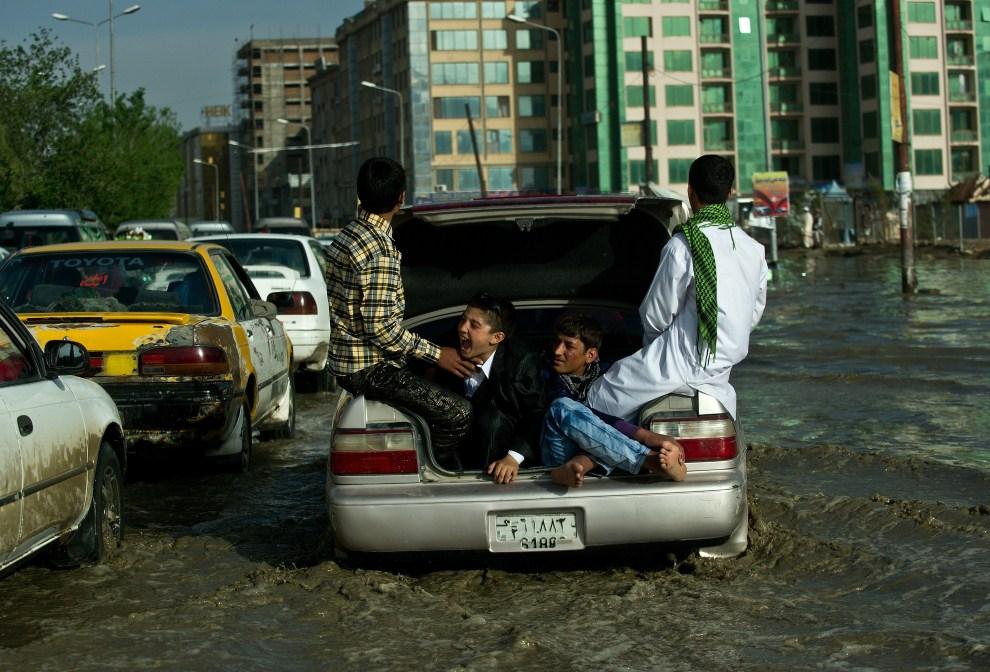 21. AFGANISTAN, Kabul, 5 maja 2011: Chłopcy w bagażniku brodzącego w wodzie samochodu. AFP PHOTO/ MANAN VATSYAYANA