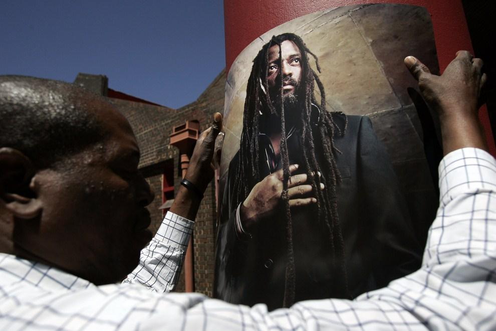 22. RPA, Johannesburg, 24 października 2007: Pracownik klubu reggae Bassline rozwiesza plakaty ze zdjęciem zabitego muzyka - Lucky Dube. AFP PHOTO / GIANLUIGI GUERCIA