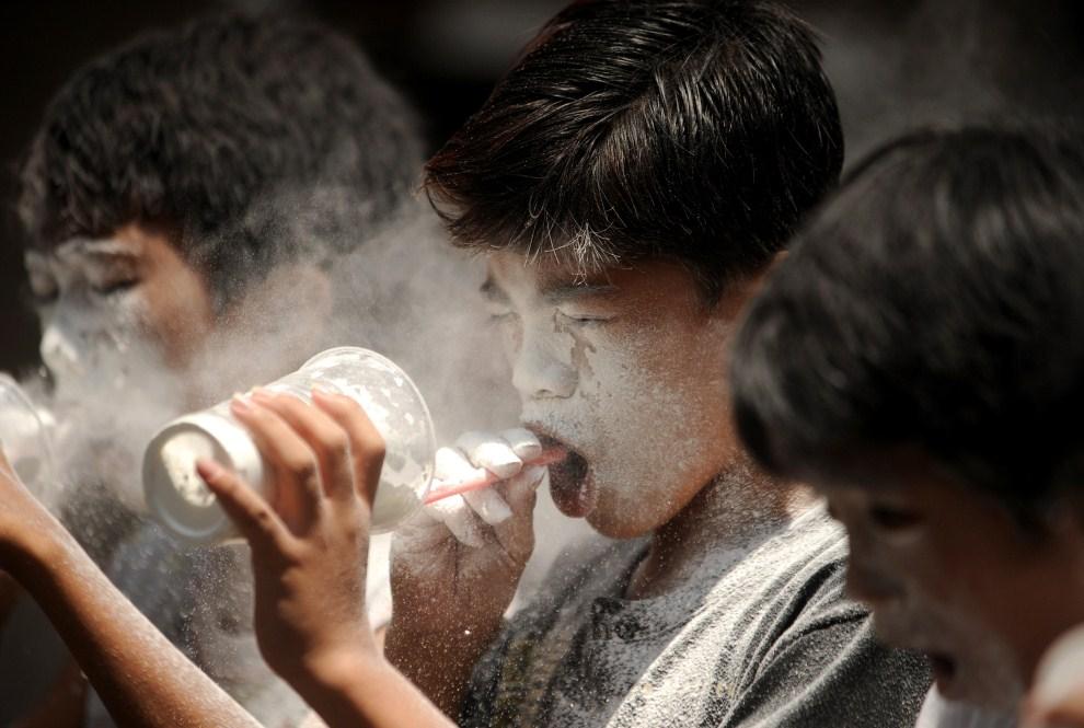 23. FILIPINY, Manila, 22 maja 2011: Dzieci wydmuchują mąką ze szklanek podczas zabawy na festynie. AFP PHOTO/NOEL CELIS