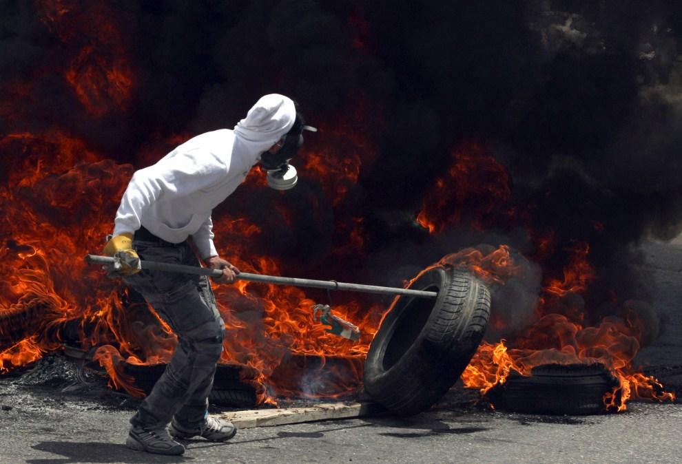 23. IZRAEL, Kalandia, 15 maja 2011: Palestyńczyk podpala barykadę z opon podczas zamieszek na przedmieściach Jerozolimy. AFP PHOTO/ABBAS MOMANI