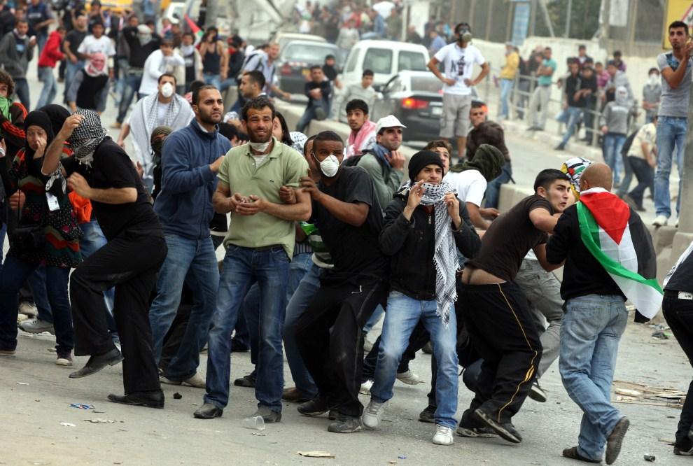 26. IZRAEL, Kalandia, 15 maja 2011: Palestyńczycy podczas walk z wojskiem. AFP PHOTO/ABBAS MOMANI