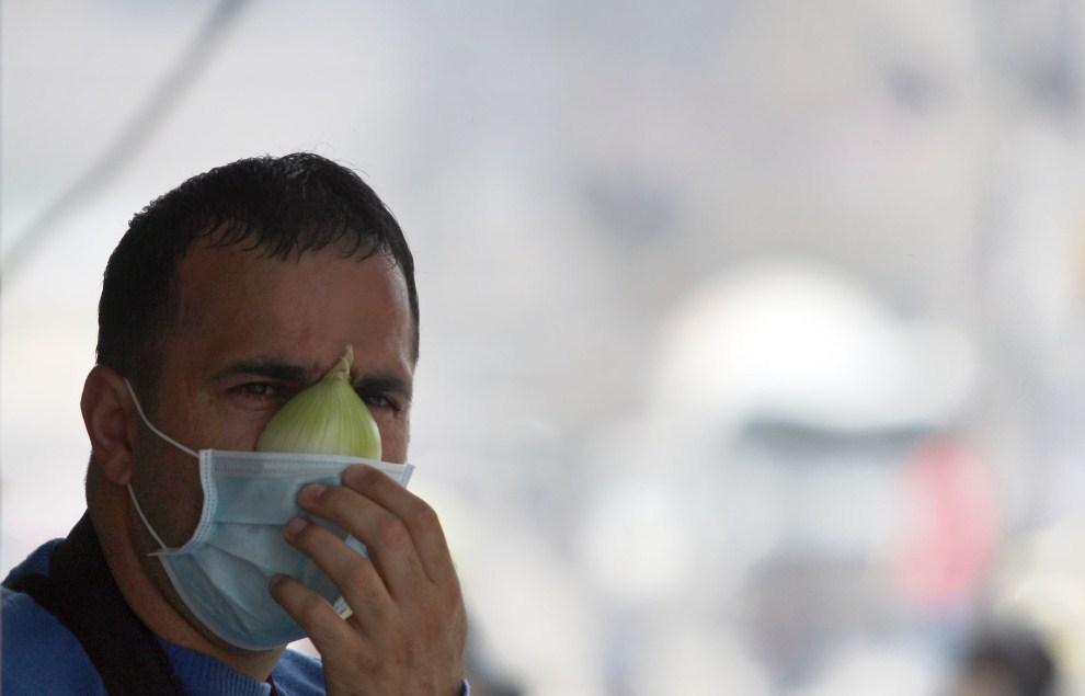 28. IZRAEL, Kalandia, 15 maja 2011: Palestyńczyk zabezpiecza się przed gazem łzawiącym zasłaniając nos i usta kawałkiem cebuli. AFP PHOTO/ABBAS MOMANI