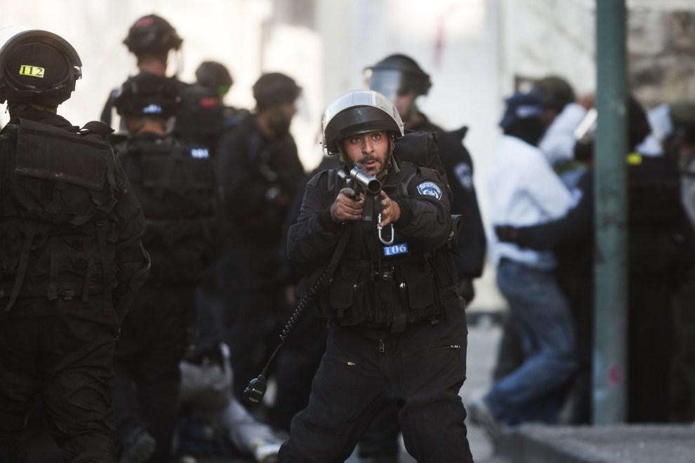 29. IZRAEL, Jerozolima, 13 maja 2011: Izraelski policjant strzela granatami z gazem łzawiącym. AFP PHOTO/MENAHEM KAHANA