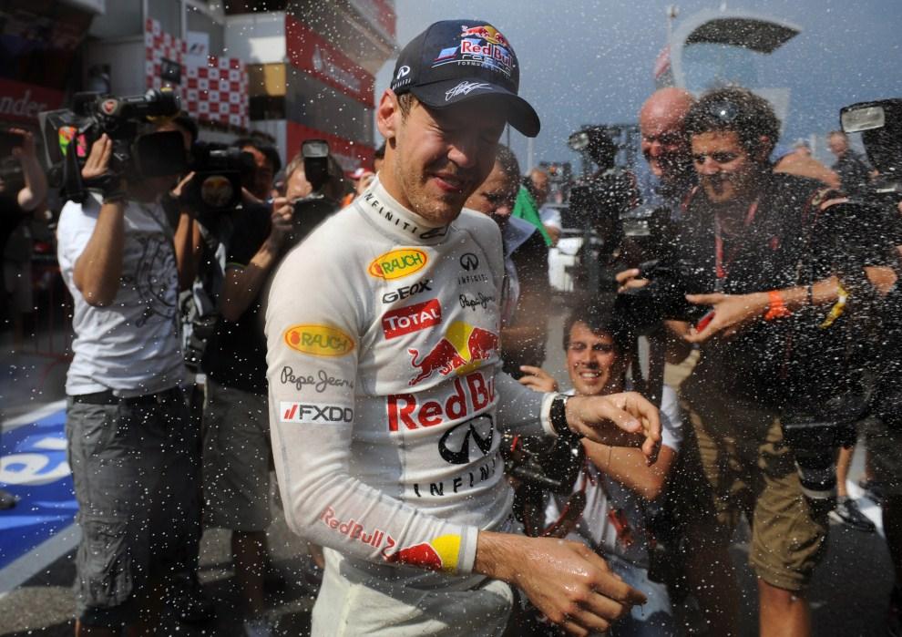 30. HISZPANIA, Barcelona, 22 maja 2011: Sebastian Vettel oblewany przez kolegów z zespołu po zwycięstwie na Circuit de Catalunya. AFP PHOTO / DIMITAR DILKOFF