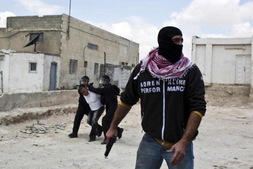 34. IZRAEL, Jerozolima, 15 maja 2011: Izraelski policjant w cywilnym ubraniu  uczestniczący w zatrzymaniu jednego z protestujących mężczyzn. AFP PHOTO/ILIYA YEFIMOVICH