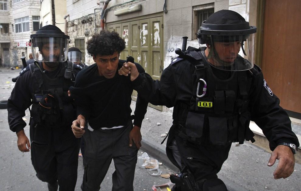 36. IZRAEL, Jerozolima, 15 maja 2011: Izraelscy policjanci prowadzą zatrzymanego podczas zamieszek mężczyznę.  AFP PHOTO /AHMAD GHARABLI