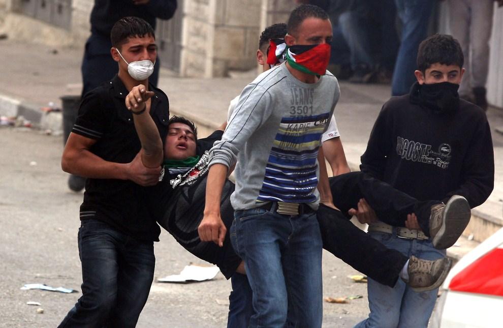 37. IZRAEL, Kalandia, 15 maja 2011: Palestyńczycy niosą rannego uczestnika zamieszek. AFP PHOTO/ABBAS MOMANI