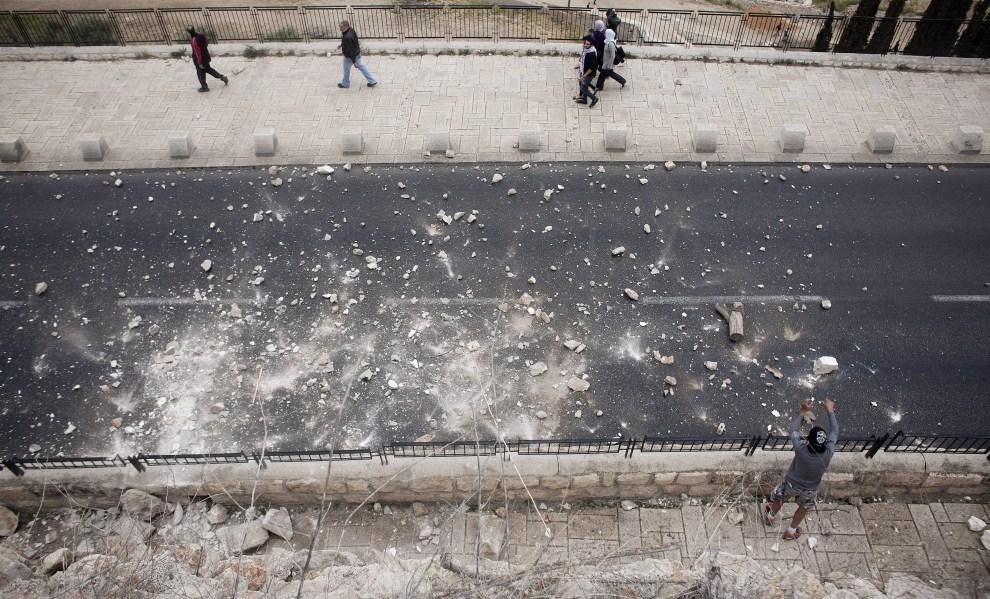38. IZRAEL, Jerozolima, 14 maja 2011: Turyści mijają Palestyńczyka zrzucającego kamienie na ulicę. EPA/OLIVER WEIKEN/PAP/EPA.