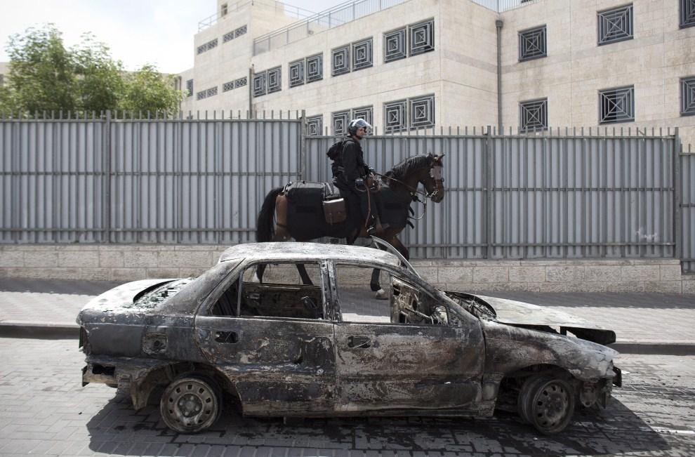42. IZRAEL, Jerozolima, 13 maja 2011: Izraelski żołnierz mija samochód podpalony podczas zamieszek. EPA/OLIVER WEIKEN/ PAP/EPA.