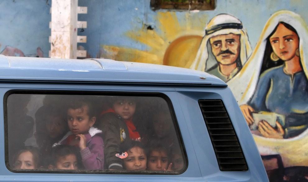 44. STREFA GAZY, 14 maja 2011: Palestyńskie dzieci przejeżdżają obok graffiti przedstawiającego powrót Józefa i Marii, rodziców Jezusa Chrystusa, z wygnania. AFP PHOTO / MAHMUD HAMS