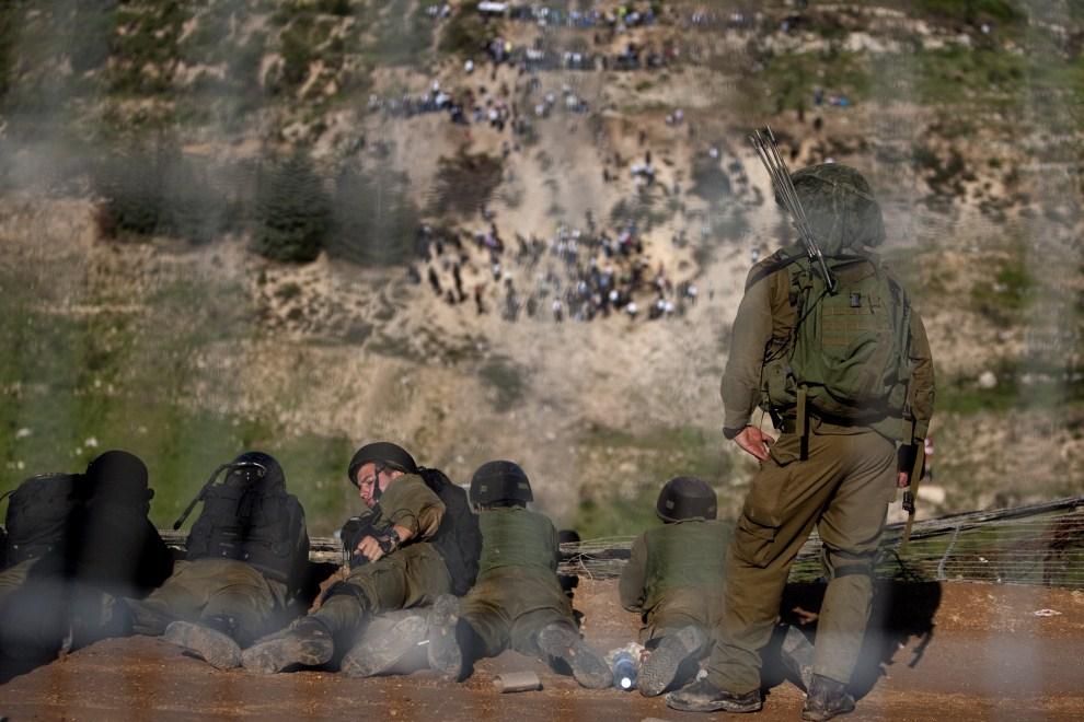 4. IZRAEL, Madżdal Szams, 15 maja 2011: Izraelscy żołnierze obserwują Palestyńczyków zebranych na Wzgórzach Golan.  AFP PHOTO/ MENAHEM KAHANA