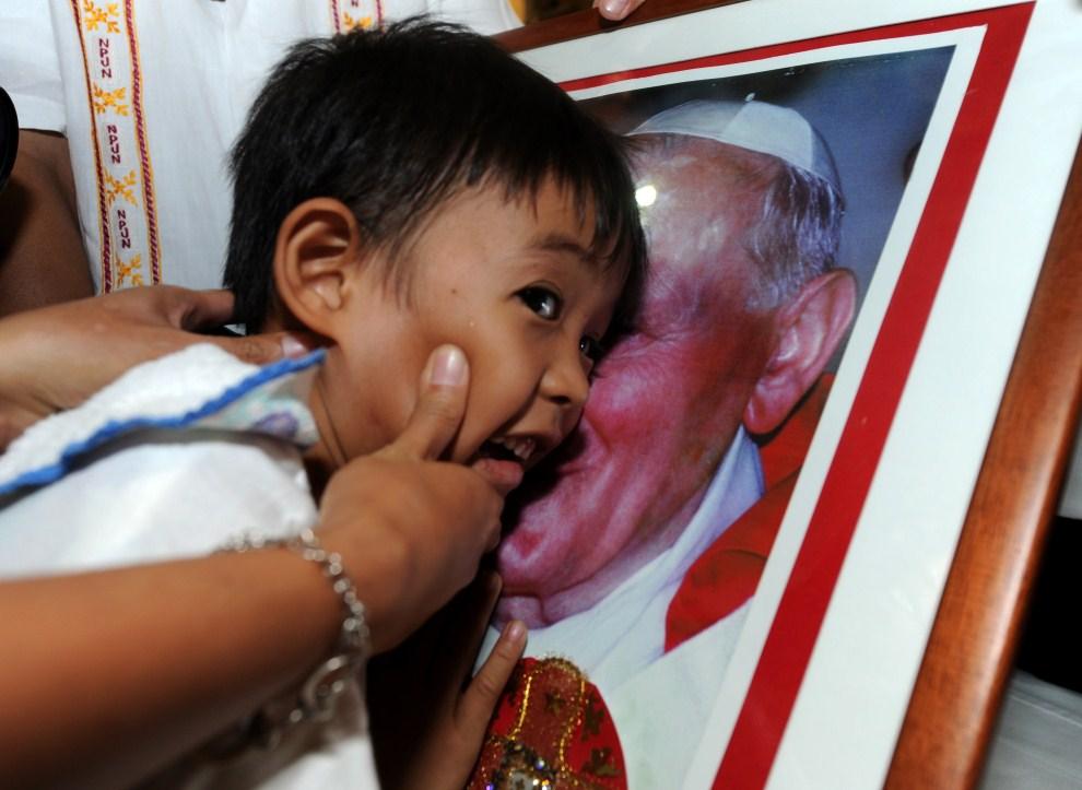 5. FILIPINY, Manila, 1 maja 2011: Matka przyciska twarz dziecka do portretu Jana Pawła II. AFP PHOTO / NOEL CELIS