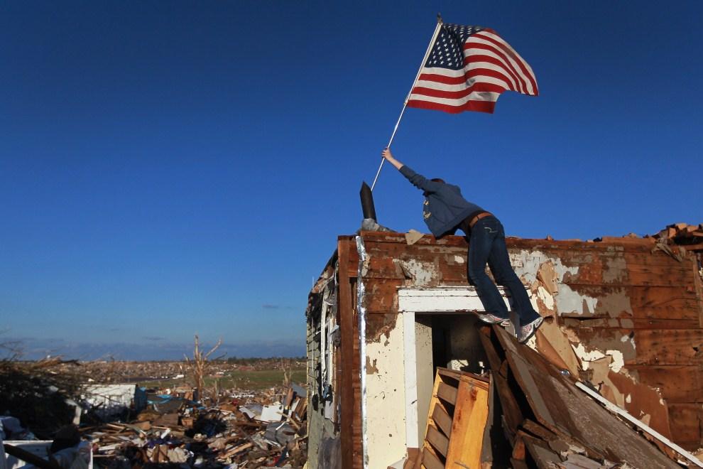 6. USA, Joplin, 26 maja 2011: Crystal Kilpatrick wbija flagę w ścianę zniszczonego domu. Joe Raedle/Getty Images/AFP