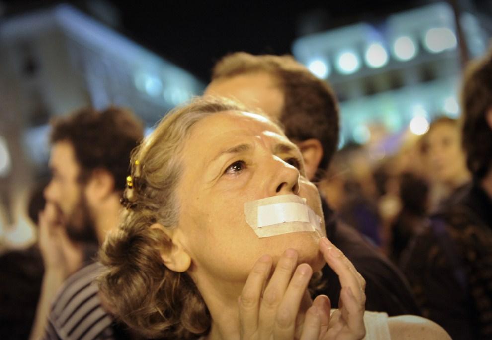 6. HISZPANIA, Madryt, 20 maja 2011: Kobieta z zaklejonymi ustami uczestnicy w wiecu potępiającym wysokie bezrobocie. AFP PHOTO / PEDRO ARMESTRE