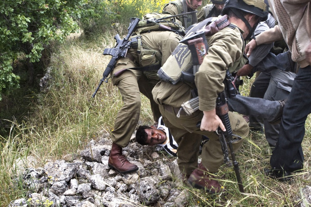 7. ZACHODNI BRZEG, Walagah, 15 maja 2011: Izraelscy żołnierze aresztują uczestnika protestów. AFP PHOTO/MENAHEM KAHANA
