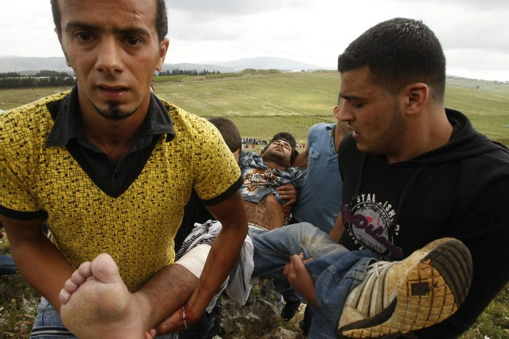 8. LIBAN, Marun Al-Ras, 15 maja 2011: Mężczyzna raniony przez izraelskich żołnierzy podczas zamieszek niesiony przez przyjaciół. AFP PHOTO/MAHMOUD ZAYAT