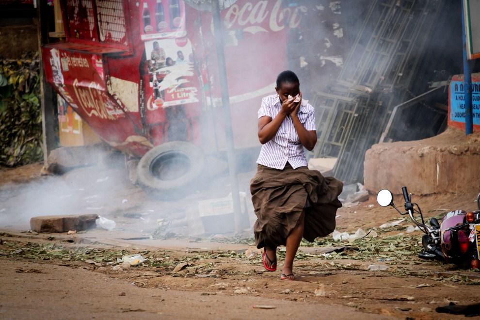 9. UGANDA, Kampala, 12 maja 2011: Kobieta zakrywa twarz przed gazem łzawiącym rozpylanym podczas manifestacji opozycji. AFP PHOTO/MARC HOFER