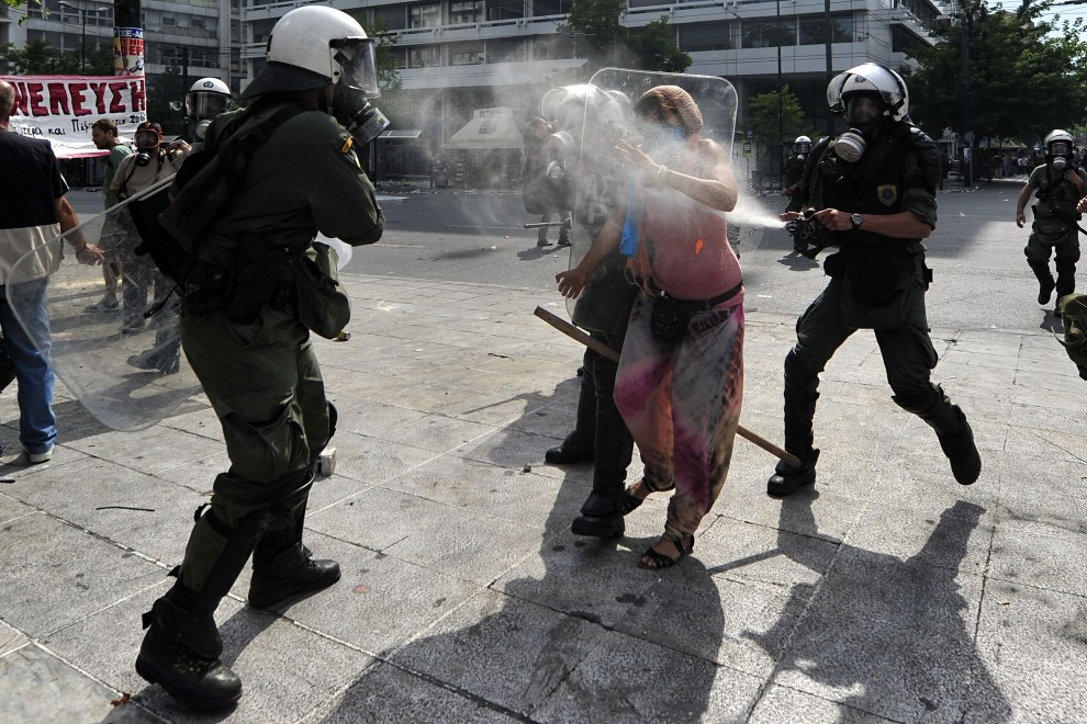 10. GRECJA, Ateny, 15 czerwca 2011: Policjanci rozpylają gaz łzawiący w kierunku protestującej kobiety. AFP PHOTO / ARIS MESSINIS