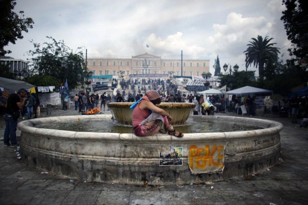 11. GRECJA, Ateny, 15 czerwca 2011: Kobieta stara się złapać oddech po tym, jak rozpylony został gaz łzawiący. AFP PHOTO / Angelos Tzortzinis