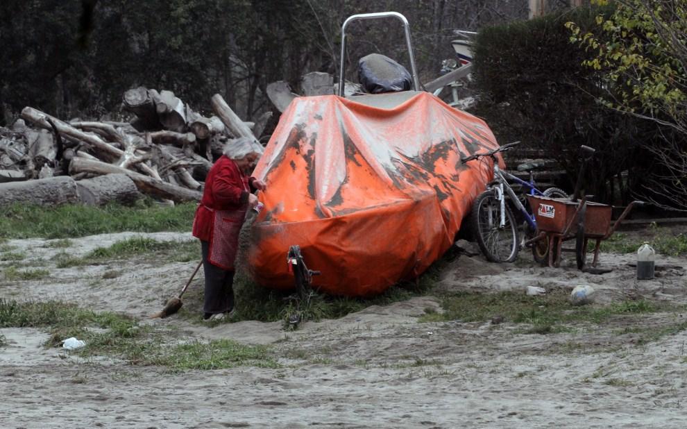11. CHILE, Puyehue, 6 czerwca 2011: Kobieta usuwa pył wulkaniczny z pokrowca łodzi. AFP PHOTO/FRANCISCO RAMOS MEJIA