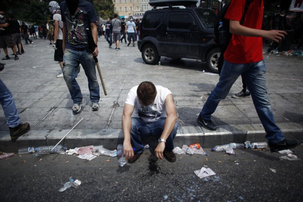 13. GRECJA, Ateny, 15 czerwca 2011: Mężczyzna, który ucierpiał w wyniku rozpylenia gazu łzawiącego. AFP PHOTO / ANGELOS TZORTZINIS