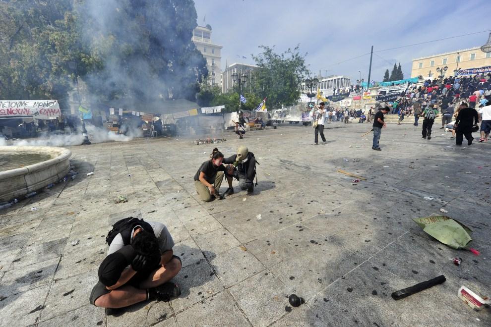 14. GRECJA, Ateny, 15 czerwca 2011: Protestujący, którzy wdychali rozpylany gaz łzawiący. AFP PHOTO / ARIS MESSINIS