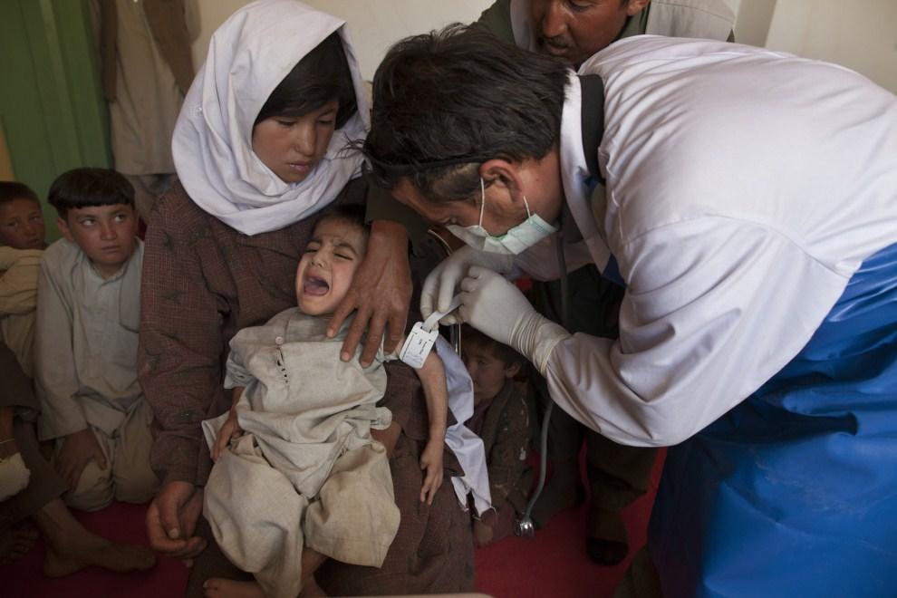 14. AFGANISTAN, Raquol, 9 czerwca 2011: Lekarz bada siedmioletnie dziecko przyprowadzone do mobilnej przychodni. (Foto: Paula Bronstein/Getty Images)